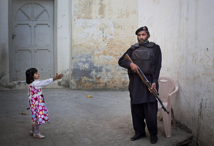 A young girl reaches out to a Pakistani policeman